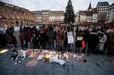 Ciudadanos encienden velas en el lugar donde falleció una de las...
