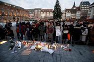 Ciudadanos encienden velas en el lugar donde falleció una de las víctimas en el atentado del martes en Estrasburgo.