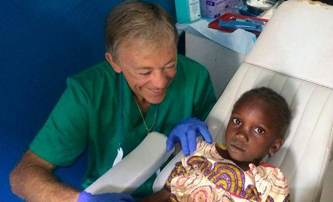 el cirujano maxilofacial Enrique Llobell con una niña a la que reparó sus molestias dentales.