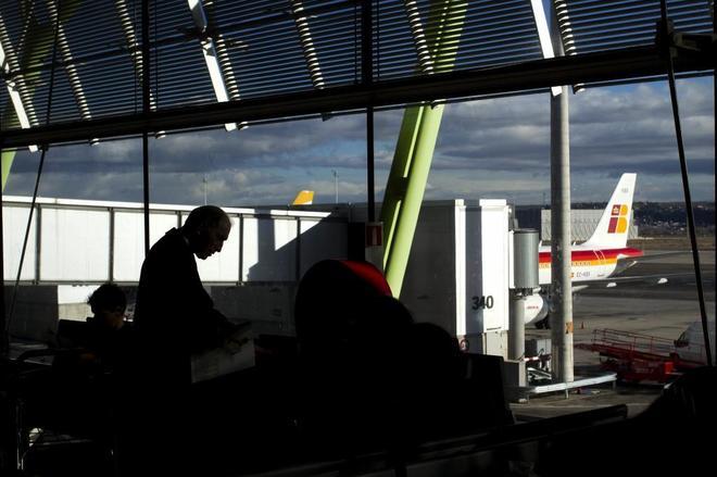 Pasajeros esperan junto a una puerta de embarque en el aeropuerto de Madrid Barajas.