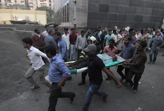 Un grupo de personas evacua a un hombre del fuego en un hospital de Bombay, este lunes.