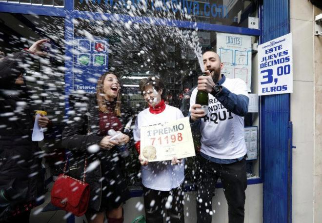 Tres personas celebran e Gordo de la Lotería de Navidad en una...
