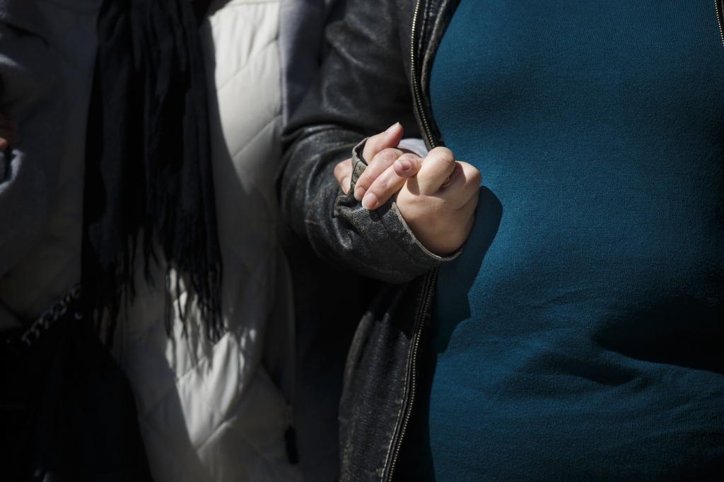 Dos personas estrechan sus manos en una concentración de duelo.