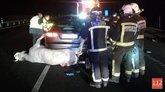 Bomberos y guardias civiles junto al coche que ha colisionado con la...