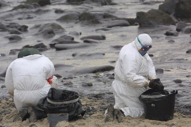 Dos voluntarios limpian la playa de Lira, en Carnota, tras el...