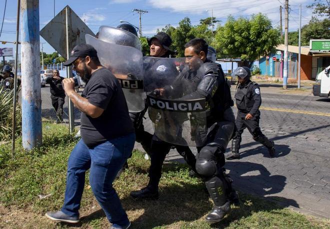 Policías nicaragüenses repliegan a un periodista en Managua.