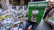 Una mujer muestra una edición de Charlie Hebdo ante la sede de la revista.