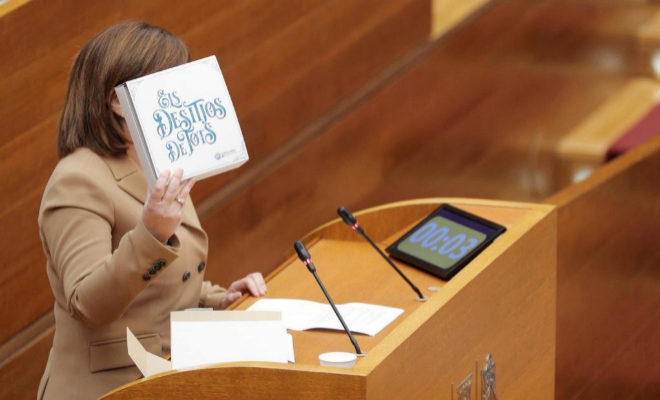 """La portavoz del grupo popular en Les Corts Valencianes, Isabel Bonig, muestra una caja con el lema """"Els desitjos de tots""""."""