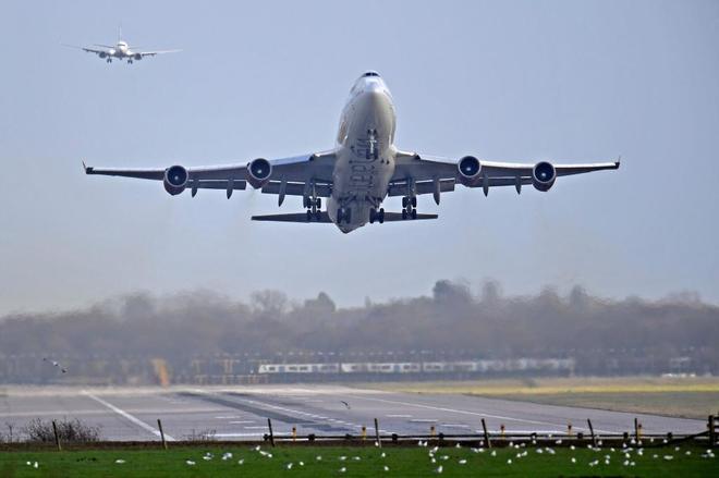 Un avión despega mientras otro se prepara para aterrizar en el aeropuerto londinense de Gatwick tras la reanudación de su actividad.
