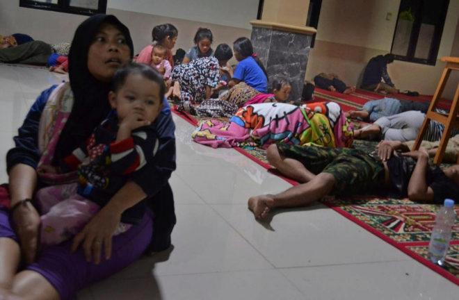 Varias personas se refugian en el interior de una mezquita, tras ser evacuadas por las fuertes olas.