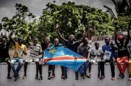 Simpatizantes de la coalición opositora portan una bandera de la República Democrática del Congo.
