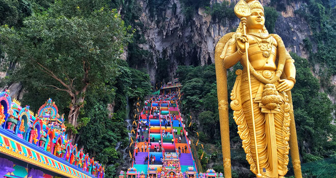 La dorada estatua del dios Murugan a los pies de las coloridas escaleras.