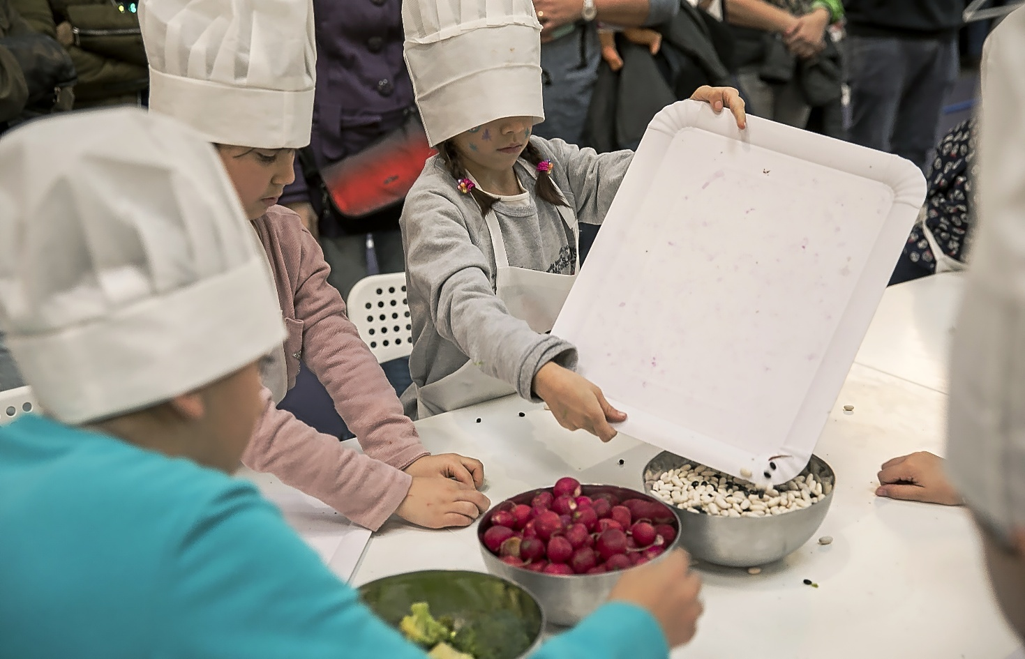 Pequeños cocineros elaborando un plato en equipo en la anterior edición de la Ciutat dels Somnis.