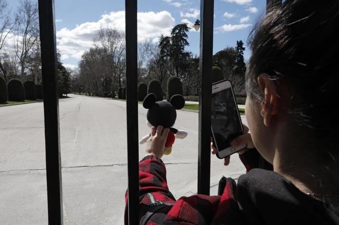Una niña hace una foto con su móvil a un muñeco en el parque del...