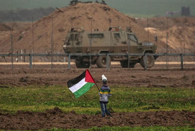 Un niño palestino muestra una bandera ante un vehículo militar...