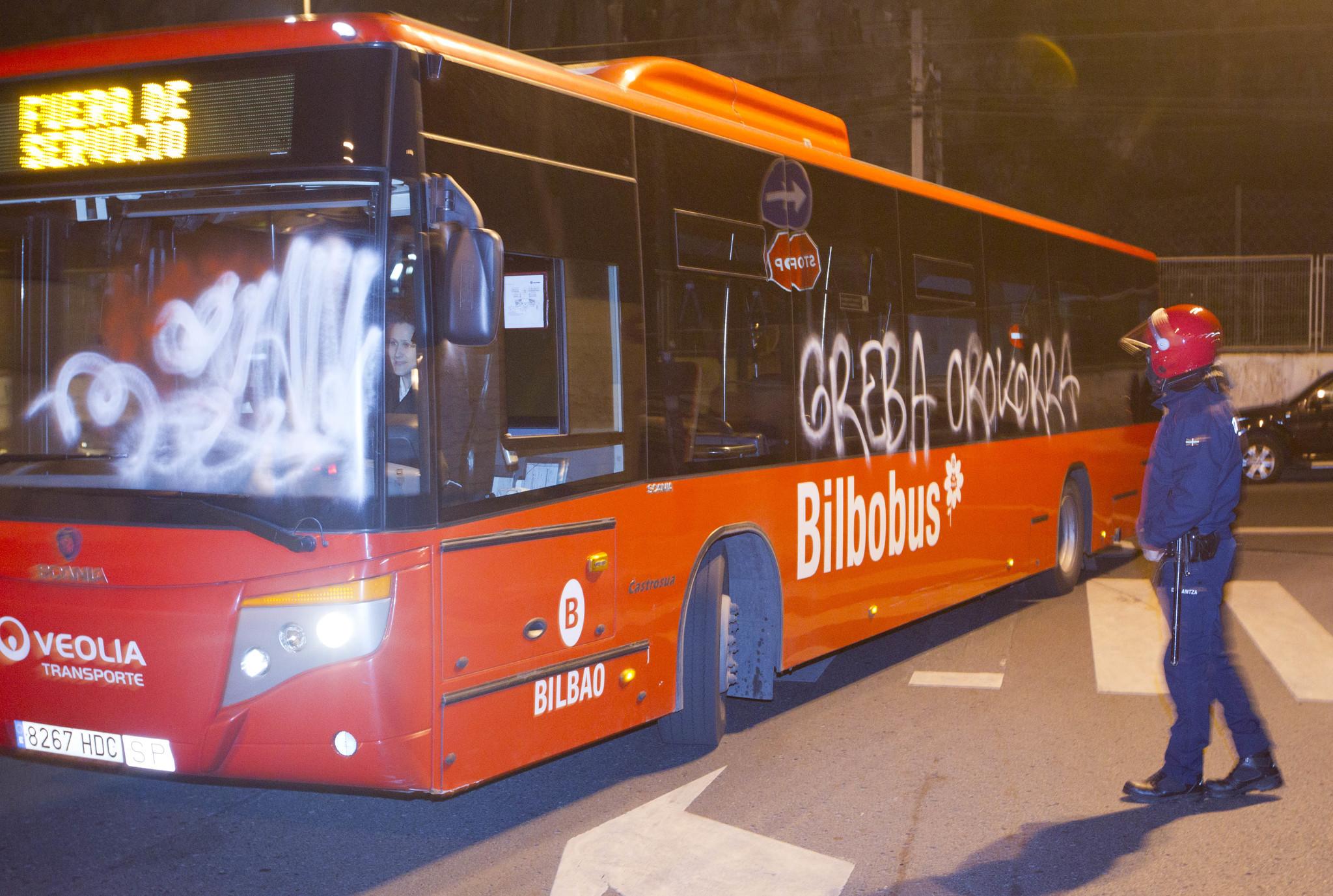Un autobús de Bilbobus es custodiado por un ertzaina durante una protesta sindical contra la reforma laboral.