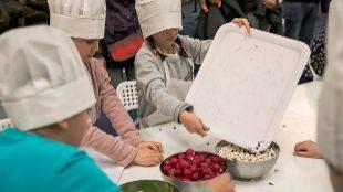 Pequeños cocineros elaborando un plato en equipo en la anterior...