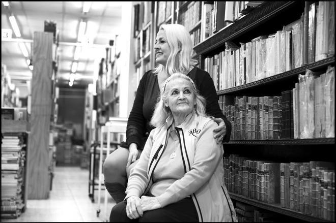 Carmela Olmos, sentada, junto a su hija Soraya, en la librería Ábaco que dirige, cercana a la glorieta de Quevedo madrileña.