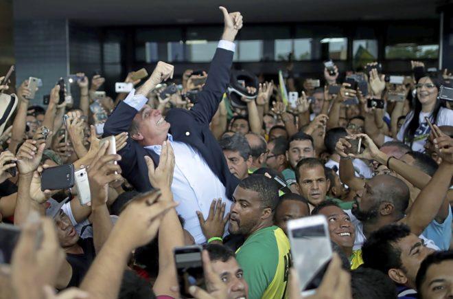 El presidente brasileño, Jair Bolsonaro, saluda a cientos de seguidores agolpados a su alrededor.