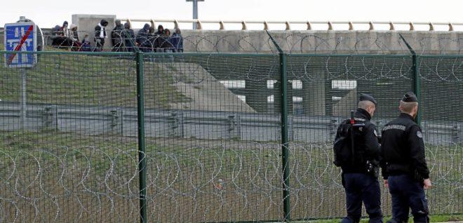 Dos policías patrullan una verja ante un grupo de migrantes en la ciudad francesa de Calais.