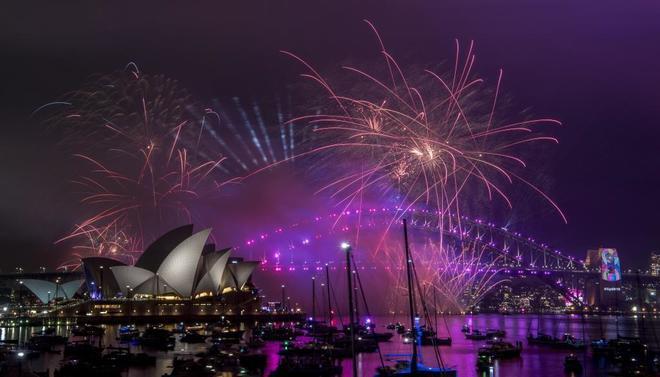 Un espectáculo de fuegos artificiales ilumina el cielo sobre el puerto de Sidney (Australia).
