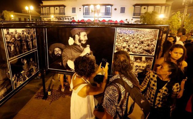 Turistas y residentes en Santiago de Cuba conversan frente a una exposición de fotografías referentes a momentos de la Revolución cubana, con imágenes del ex mandatario, el ya fallecido Fidel Castro.