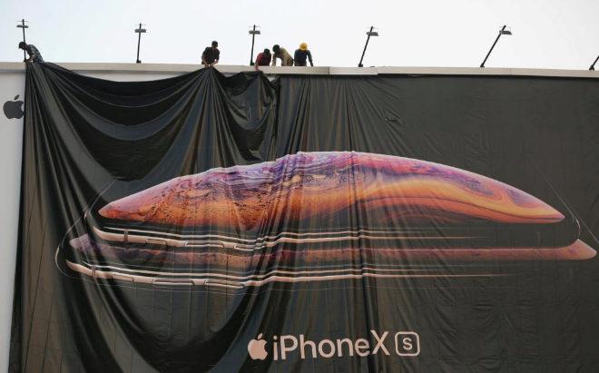 Trabajadores ajustan un cartel de promoción del iPhone XS en la India.