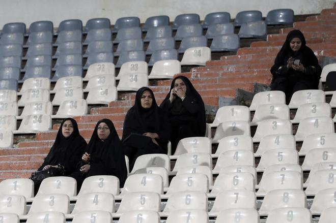 Mujeres musulmanas presencian un partido en un estadio de fútbol, en Teherán.