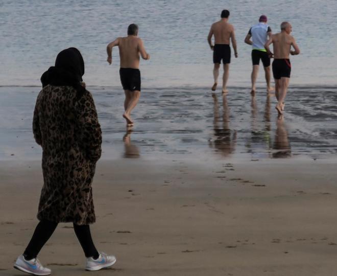 Una mujer observa a unos bañistas, hoy, en la playa Ondarreta de San...