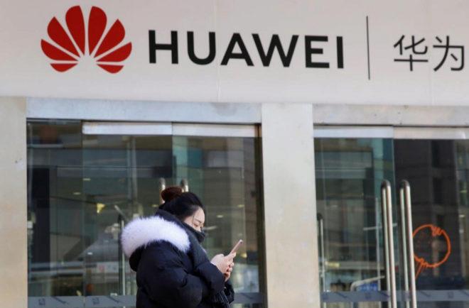 Una joven consulta su móvil delante de una tienda de Huawei.