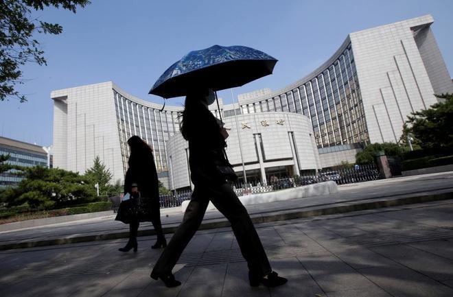 Paseantes frente al edificio del Banco Central de China.