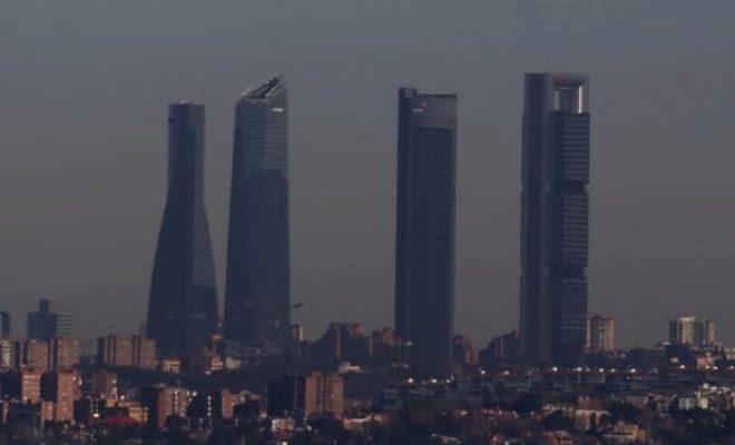 Las cuatro torres, rodeadas por la 'boína' que estos días cubre Madrid.