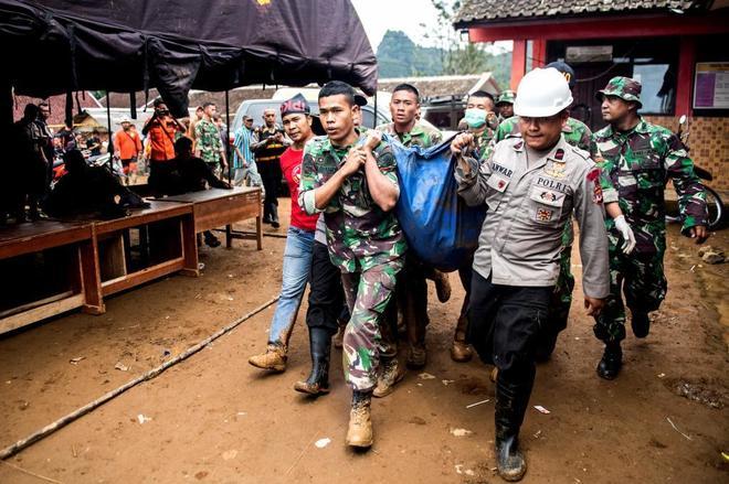 Trabajadores de grupos de rescate trasladan un cadáver tras una avalancha en Java, Indonesia.