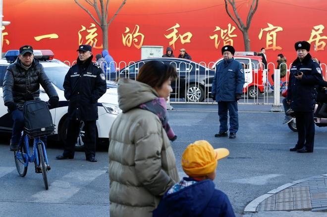 Una mujer recoge a un niño del colegio en el que tuvo lugar el ataque, en Pekín, China.