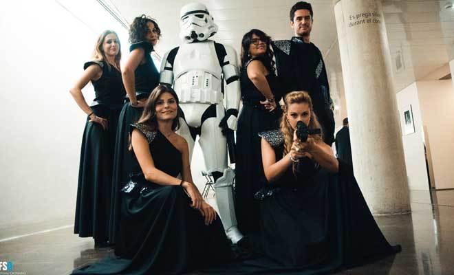 Algunos de los músicos de la Film Symphony Orchestra posan antes de un concierto con un soldado de choque de 'La guerra de las galaxias'.