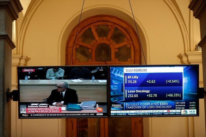 Detalle de las pantallas de televisión de la Bolsa de Madrid, con la comparecencia de Rodrigo Rato en el juicio por Bankia.