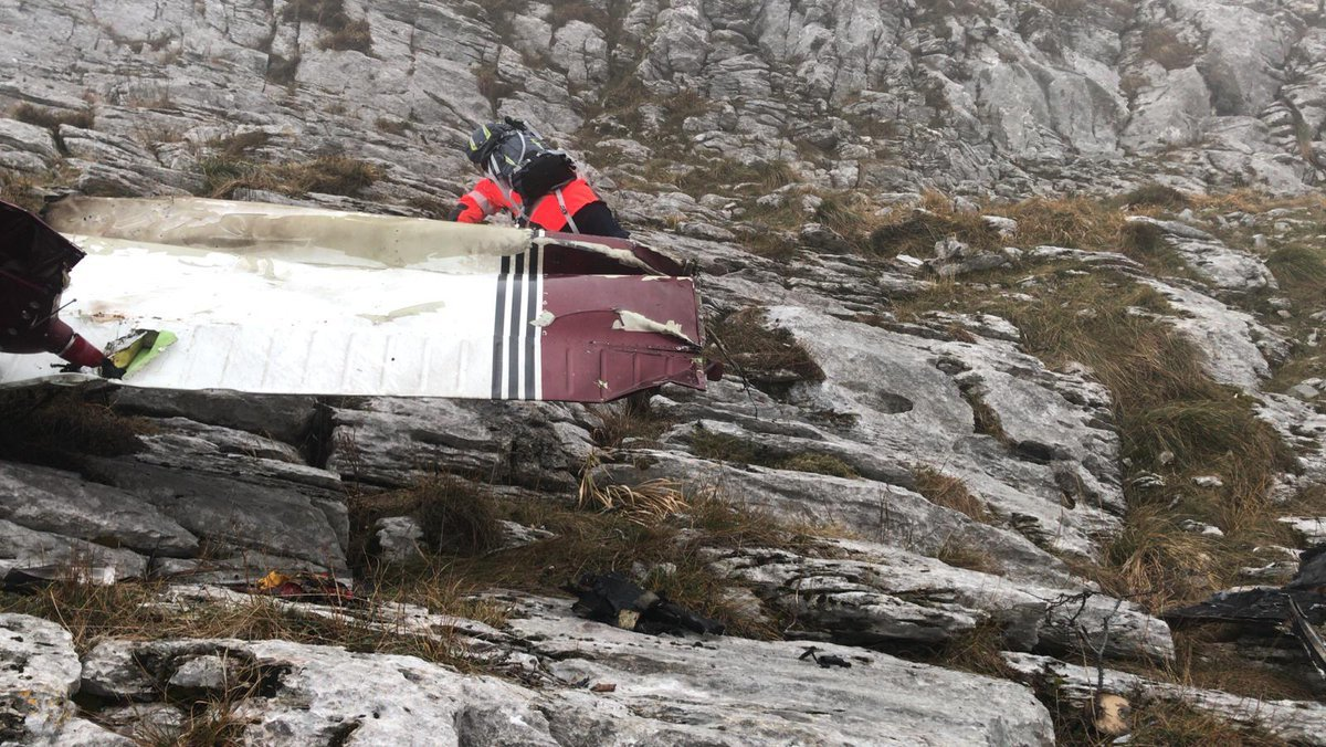 Uno de los miembros de rescate, junto a un ala de la avioneta.