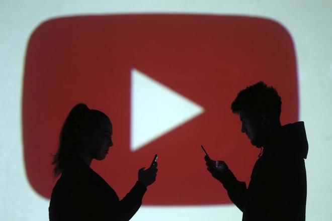Usuarios delante del logo de YouTube, plataforma propiedad de Google.