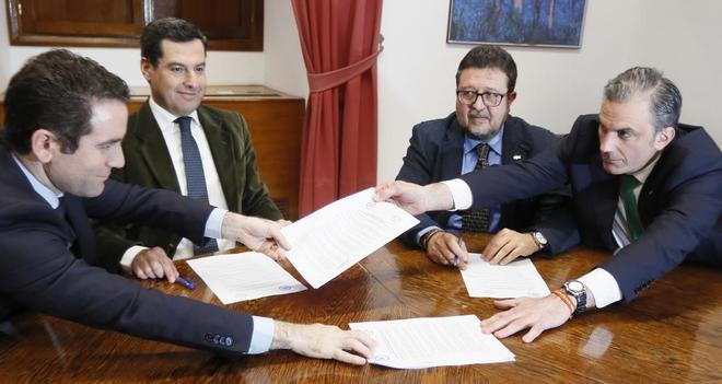 Teodoro García Egea, Juan Manuel Moreno, Francisco Serra y Javier Ortega (de izqda. a dcha.) intercambian documentos para la firma.