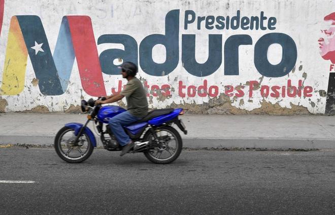 Un motorista circula frente a un mural de Maduro en Caracas, Venezuela.
