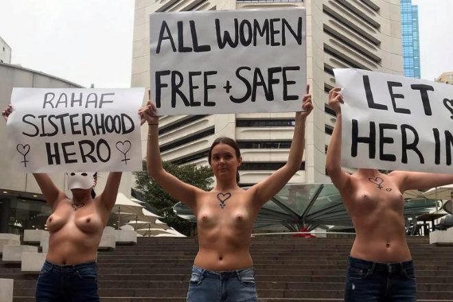 Mujeres con el pecho descubierto sostienen carteles en apoyo de la joven saudí retenida en Bangkok