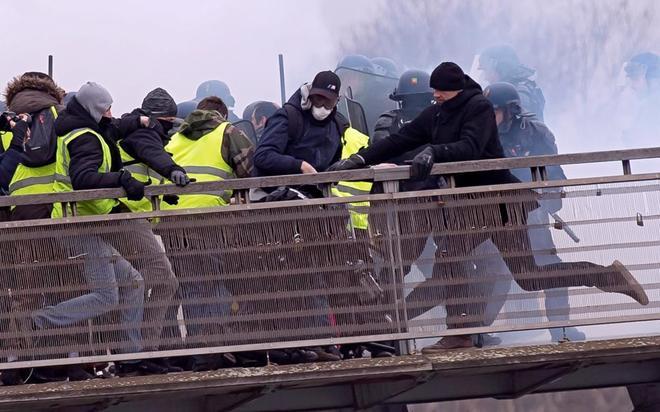 El ex campeón de boxeo Chistophe Dettinger patea a un gendarme durante una manifestación en París.