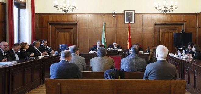 De espaldas, los acusados, en el banquillo, ante el tribunal de la Audiencia de Sevilla que los está juzgando.