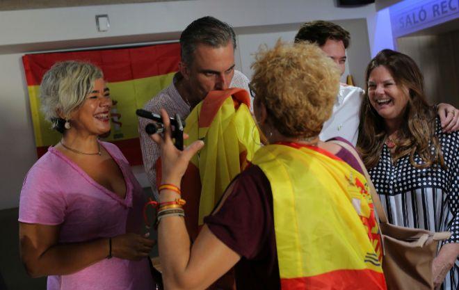 Javier Ortega besa una bandera de España rodeado de mujeres.