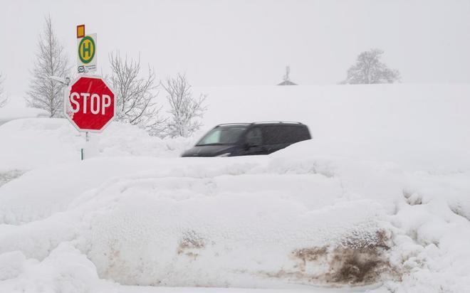 Un vehículo circula por una carretera cubierta de nieve en Reitham, Baviera, Alemania.