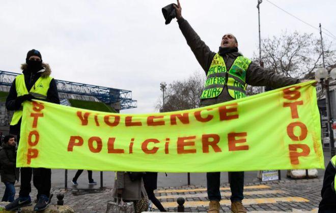"""Dos 'chalecos amarillos' portan una pancarta con la frase """"Stop a la violencia policial"""" en Bercy."""