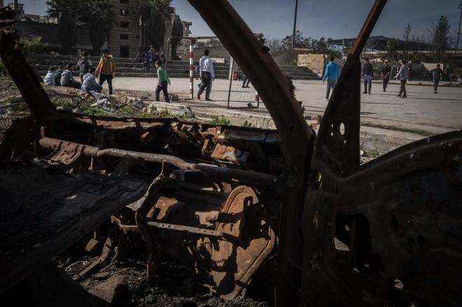 Jóvenes juegan al fútbol entre las ruinas de la violencia del IS en Raqqa.