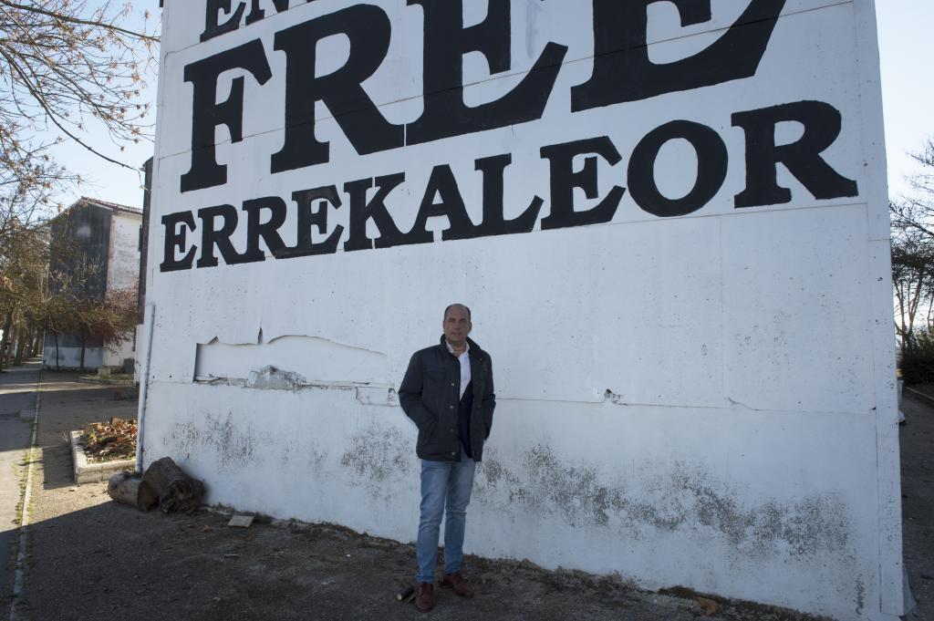 El concejal del PP, Mikel Garnica, junto a una pintada okupa de Errekaleor.