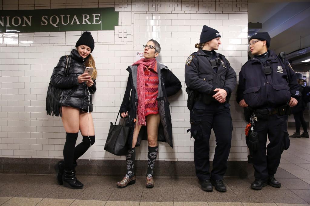Dos mujeres posan junto a dos agentes en el metro de Nueva York.