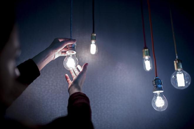Un hombre enciende una bombilla de ahorro de energia.